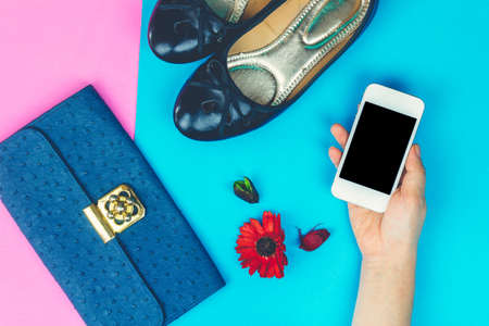 Women hand holding smartphone with outfit of casual and woman fashion