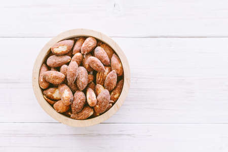 Almonds in bowl on  wooden background Stock Photo