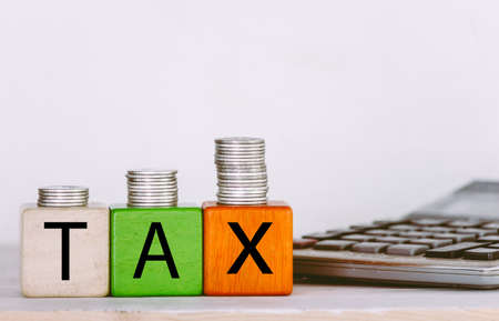 Tax Concept with wooden block with stacked coins
