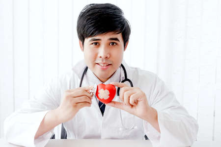 Male doctor with stethoscope holding red heart