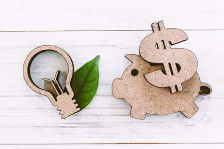 Lamp and piggy bank on wooden background - Energy saving concept