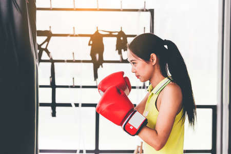 Woman punching bag with boxing gloves Stock Photo