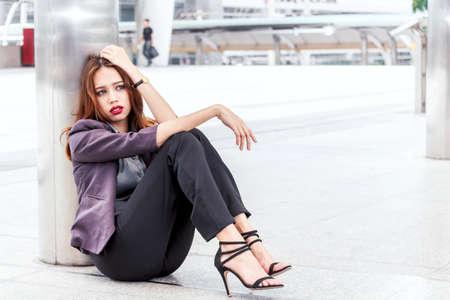 Unemployed businesswoman sit on the floor Stock Photo