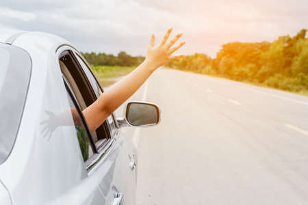 Woman hand in the car relaxing and happy traveler on the road