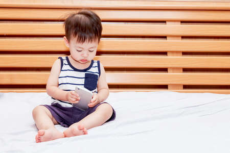Baby boy holding smartphone on bed