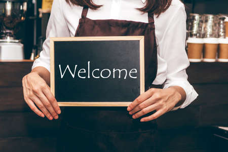 Barista holding chalkboard with word WELCOME in coffee shop restaurant