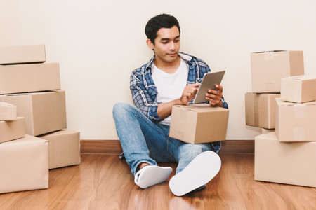 Young man with cardboard box at home - Business online and delivery concept
