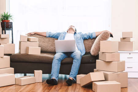 Man working overload and sleep near cardboard boxes around