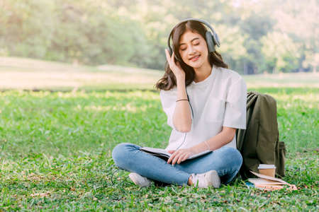 Woman relax with headphones listening to music sitting on grass in park