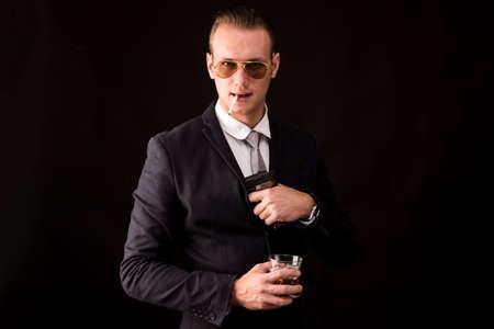 Portrait of young businessman holding gun on dark background
