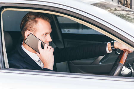 Businessman use smartphone while driving the car Stock Photo