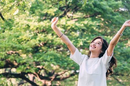 Woman standing stretch her arms relax and enjoy with nature fresh air