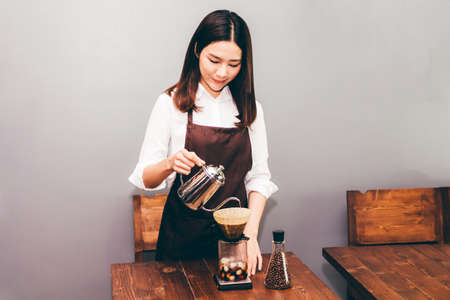 Women Barista making drip coffee in the cafe