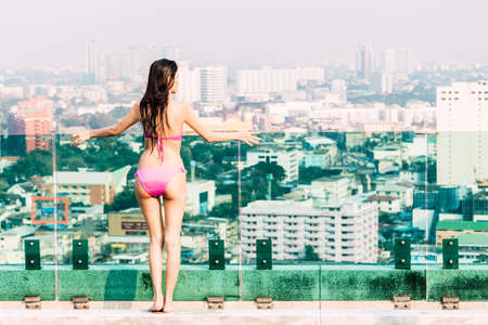 Woman wearing two piece bikini in summer vacation relaxing on city background 写真素材