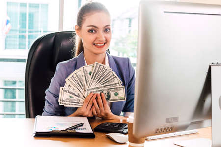 Businesswoman holding money dollar banknotes at office