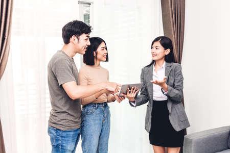 Immobilienmakler hält Tablette und sprechen mit jungem Paar in einem Haus zum Verkauf. Geschäfts- und Immobilienkonzept