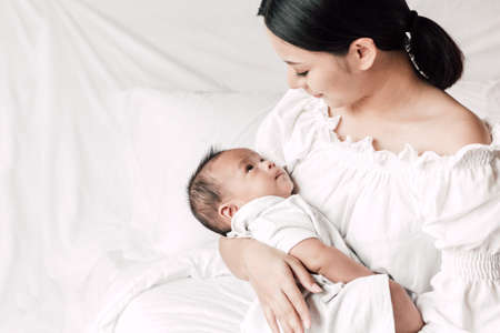 Mother holding baby in her arms in a white bedroom.Love of family concept