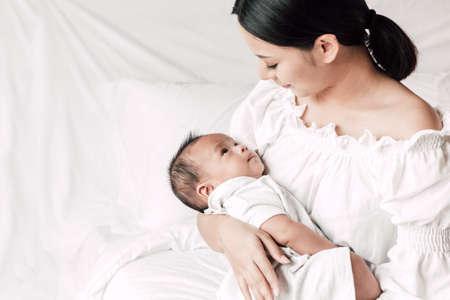 Moeder bedrijf baby in haar armen in een witte slaapkamer. Liefde van familie concept Stockfoto