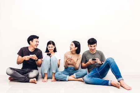 Group of friend sitting relax use technology together of smartphone checking social apps against copy space background.Communication concept
