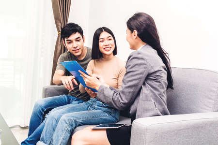 Real estate agent holding documents to sign agreement paper to couple for signature in a house for sale.Young couple signing contract.business and real estate concept