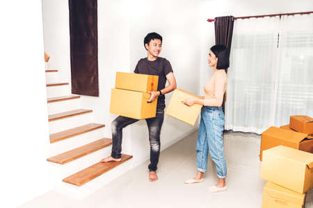 Happy young couple carrying boxes and moving into their new home.House moving and real estate concept 写真素材