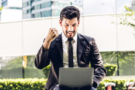 Successful of handsome businessman in black elegant suit sitting celebrating with arms up and working with laptop computer on the city.Business and startup