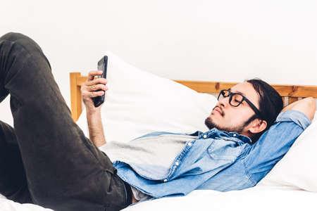 Man ontspannen gebruiken en praten door smartphone op het bed thuis. Technologie en communicatieconcept Stockfoto