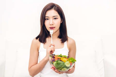 Happy woman eating and showing healthy fresh salad in a bowl.dieting concept.healthy lifestyle with green food