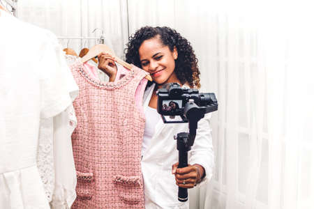 African american woman blogger standing in front of camera recording herself shopping and choosing clothes in a store.fashion shopping and social media concept