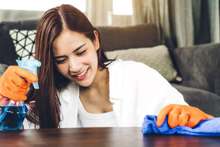 Young woman in protective gloves using a spray and rag while cleaning home in living room at home.housework and home cleaning concept