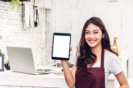 Portrait of woman small business owner smiling and standing with tablet computer in the cafe or coffee shop.woman barista standing at cafe