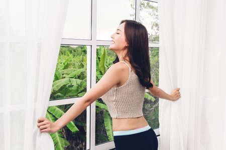 Vrouw wordt wakker en opent raamgordijnen en ze voelt zich 's ochtends gelukkig en ontspannen en ademt frisse lucht in Stockfoto