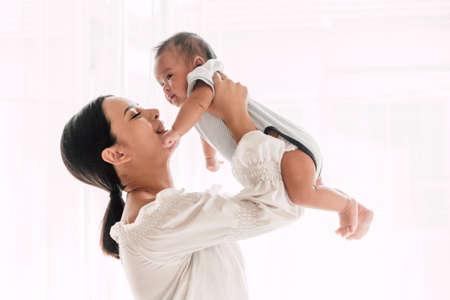 Madre sosteniendo al bebé en sus brazos y beso en un dormitorio blanco.Amor del concepto de familia