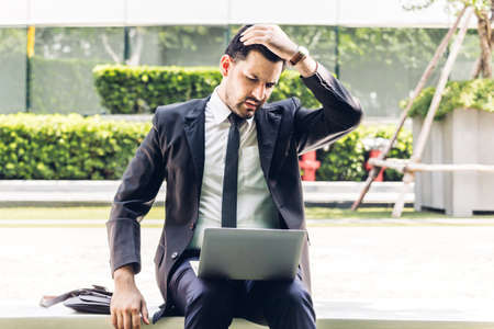 Handsome businessman in black elegant suit sitting and working with laptop computer on the city.Business and startup idea concept