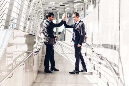 Successful business team giving a high fives gesture at city background