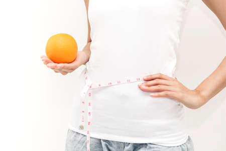 Woman holding orange and measuring her waist by measure tape Stock Photo