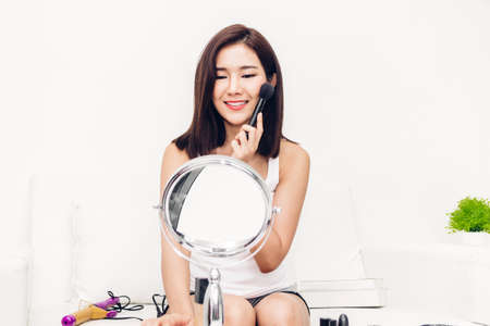 Smiling young beautiful asian woman fresh healthy skin applying makeup brush and looking on mirror at home.facial beauty and cosmetic concept