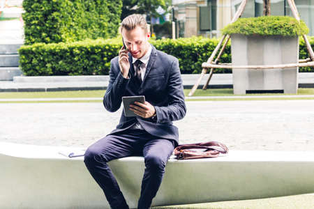 Handsome businessman in black elegant suit sitting and working with tablet computer on the city.Business and technology concept