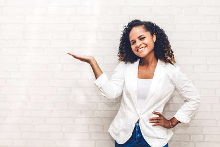 Smiling beautiful professional business african american black woman showing empty copy space on open hand standing near white brick wall background