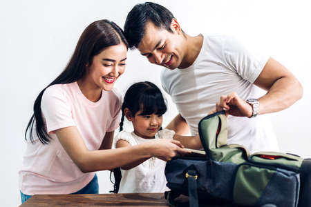 Happy family father and mother with daughter packing school bag with books before going to school at home