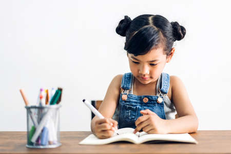 School kid little girl learning and writing in notebook with pencil making homework at home.Education concept