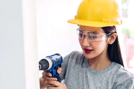 Young woman construction worker working with screwdriver to drill in a house entrance Reklamní fotografie