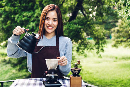 Women Barista making drip coffee in the park