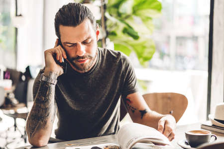 Handsome bearded hipster man use smartphone and reading book with coffee at table in cafe.Communication and technology concept