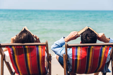 Romantic lovers young couple relaxing sitting together on the tropical beach and looking to the sea.Summer vacations Stock Photo
