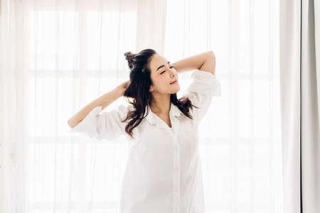 Frau, die glücklich und entspannt streckt, nachdem sie morgens zu Hause aufwacht Standard-Bild