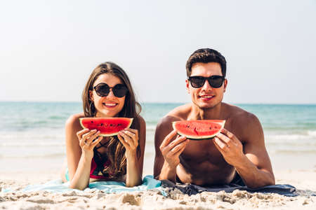 Romantic lovers young couple relaxing holding and eating a slice of watermelon on the tropical beach.Summer vacations