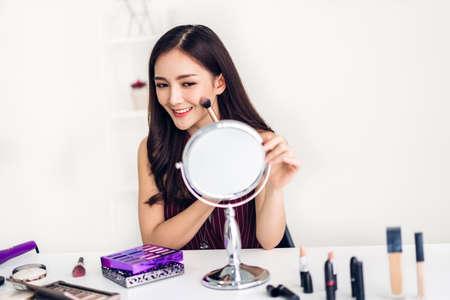 Lächelnde junge schöne asiatische Frau frische gesunde Haut, die auf Spiegel schaut und Make-up-Pinsel mit Kosmetik zu Hause hält. Gesichtsschönheit und kosmetisches Konzept
