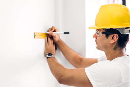 Young construction engineer in a yellow helmet working and  looking job for planning project at building home site Stock Photo