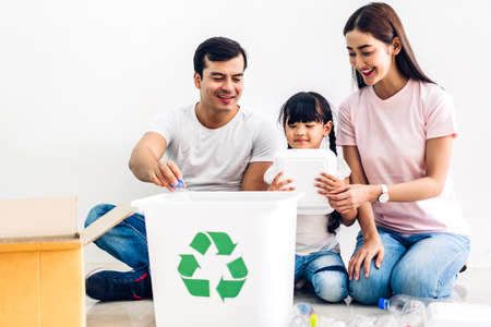 Happy smiling family having fun putting empty recycling plastic bottles and paper into the recycle box Stock Photo